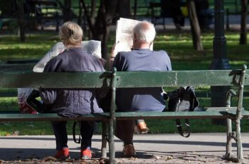 Old People Reading News Papers Sitting On Bench